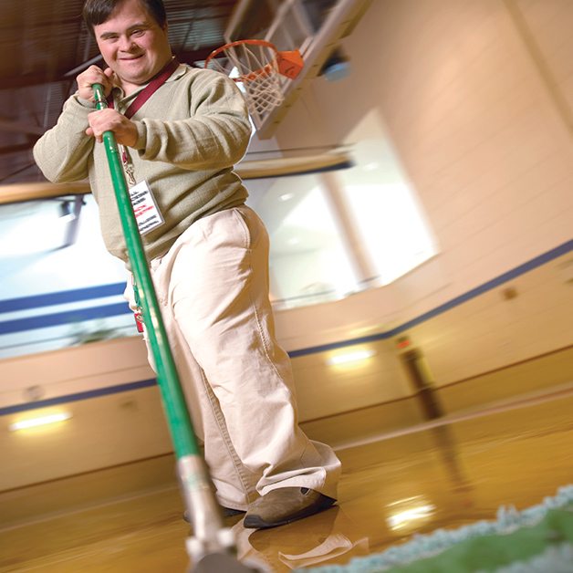 Depicts a man in a brown uniform and an employee badge in a gymnasium with a basketball hoop behind him and he is cleaning the floor with a mop