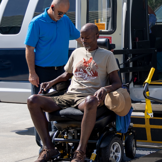 Picture of a man in a blue uniform out side of a van with a man in a power wheelchair being assisted on or off a lift