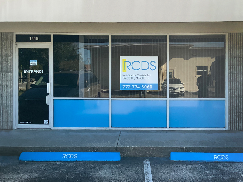 Depicts front of Vero Beach office, 3 large windows and entrance door, with large RCDS sign and phone number 772-773-3060, above the door is 1416